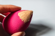 canvas print picture - Woman hand holding pink beauty blender with the beige liquid foundation on it - Image