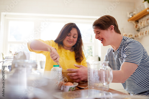Photo  Young Downs Syndrome Couple Baking In Kitchen At Home