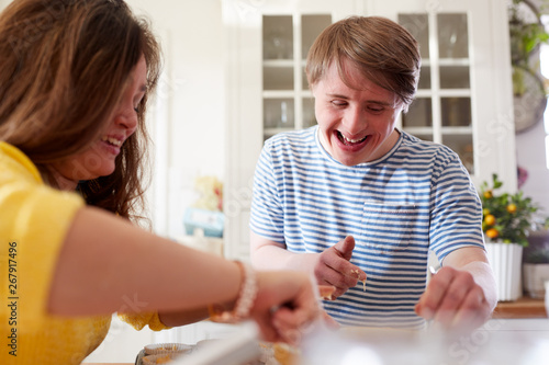 Valokuvatapetti Young Downs Syndrome Couple Baking Cupcakes In Kitchen At Home