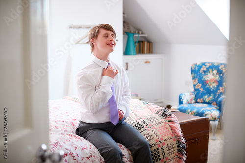 Valokuvatapetti Young Downs Syndrome Man Sitting On Bed Getting Dressed For Work