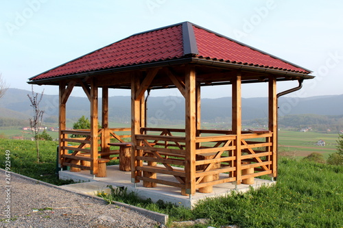 Obraz na plátně Newly built wooden gazebo structure with new roof mounted on concrete foundation