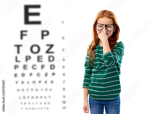 Foto auf Leinwand Texturen education, vision and childhood concept - smiling red haired student girl in glasses and green striped shirt over eye test chart background