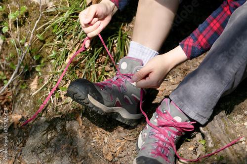 トレッキングシューズの靴ひもを結ぶ女性