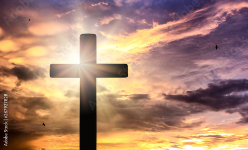 Fotografía Silhouette of crucifix cross at sunset time with holy and light background