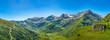 Panorama einer Bergkette mit saftigen Wiesen und massiven Felsen im idyllischen Salzburger Land unter blauem Himmel.