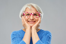 Party Props, Photo Booth And Old People Concept - Portrait Of Amazed Smiling Senior Woman In Blue Sweater With Big Glasses Over Grey Background