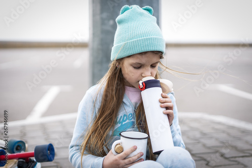 Vászonkép  A girl in a blue sweater and hat was riding a longboard and sat down on the curb to drink hot tea from a thermos