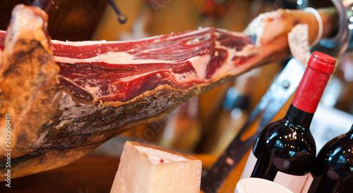 Fotografía Still life of spanish pork jammon on holder, bottles of wine cheese and olives