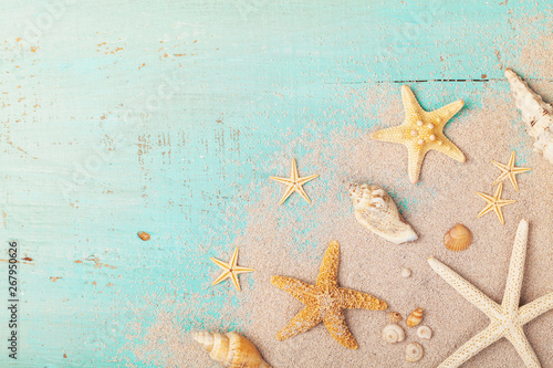 Fototapeta Starfishes and seashells on sand for summer holidays and travel background