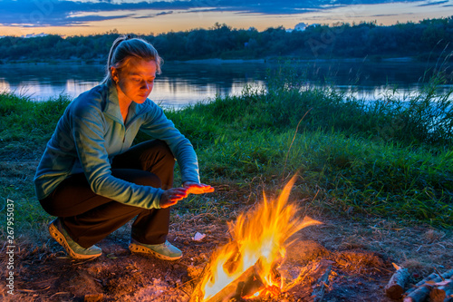 Spoed Fotobehang Kamperen Young woman is warming by the fire in camping near the river