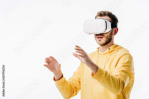 young man in yellow hoodie using virtual reality headset isolated on white