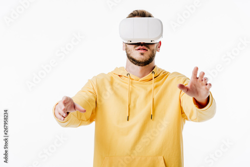 front view of young man in yellow hoodie using virtual reality headset isolated on white