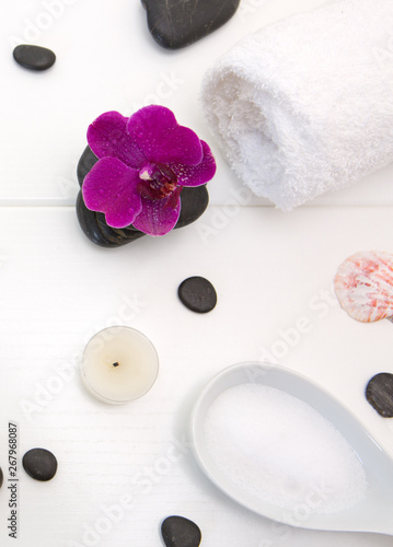 Photo  Spa setting with pink orchids , black stones and candle on wood background
