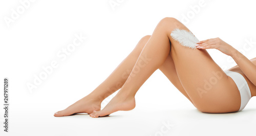 Fotografie, Obraz  Smooth and slim tanned female legs isolated on white