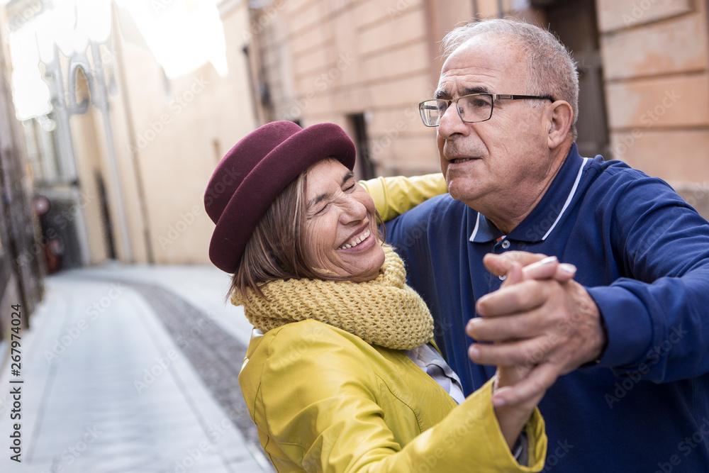 Fototapeta coppia di anziani balla felice in mezzo a una strada