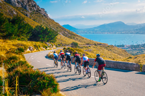 Fototapety, obrazy: Sporty friends on bicycle on sunset light in beautiful nature by the sea. Road cycling on the coast. Sport in Nature background. Teamwork concept photo