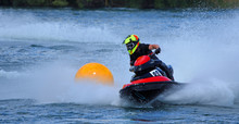Jet Ski Competitor Cornering At Speed Around Yellow Buoy Creating At Lot Of Spray.