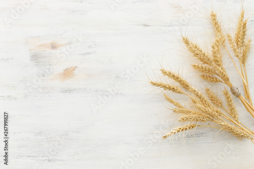 Fotografiet top view of wheat crops over white wooden background