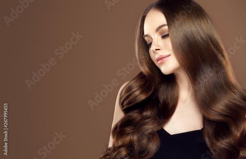 Piękna dziewczyna o długich i lśniących falowanych włosach. Piękna kobieta model z kręconymi fryzury.