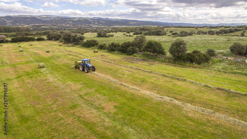 bird eye of Man at work on the tractor with hay baler Canvas Print