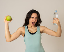 Portrait Of Attractive Latin Fitness Model With Apple And Water Feeling Healthy And Fit.