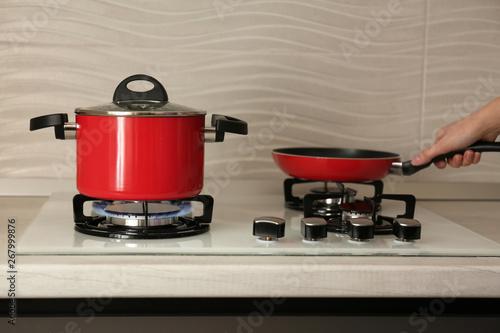 Fototapeta Woman putting frying pan near red pot on modern gas stove, closeup obraz