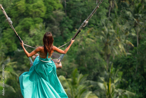 Photo  Woman in long turquoise dress swinging in the jungle, Bali