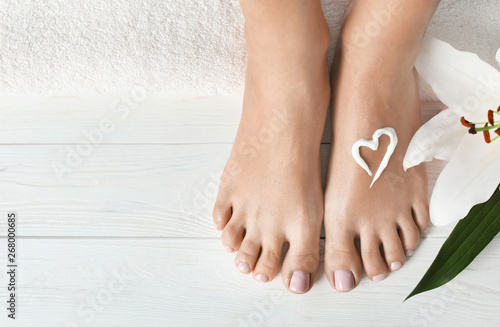 Poster Pedicure Woman with beautiful feet, cream, flower and towel on white wooden floor, closeup. Spa treatment
