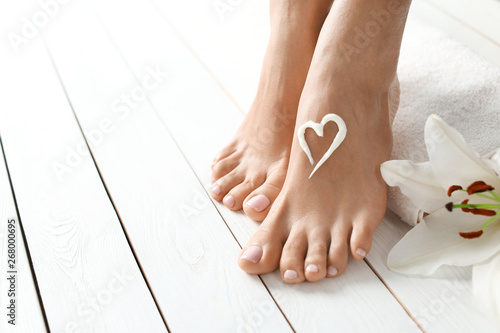 Poster Pedicure Woman with beautiful feet, cream, flower and towel on white wooden floor, space for text. Spa treatment