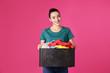 Leinwandbild Motiv Happy young woman holding basket with clothes on color background
