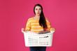Leinwandbild Motiv Displeased young woman holding basket with laundry on color background