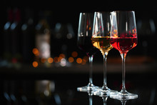 Row Of Glasses With Different Wines On Bar Counter Against Blurred Background. Space For Text