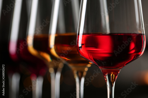 Row of glasses with different wines on blurred background, closeup