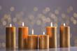 Leinwandbild Motiv Burning gold candles on table against blurred lights. Space for text