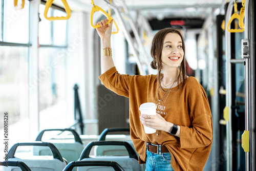 Fototapeta Young and happy passenger enjoying trip at the public transport, standing with coffee in the modern tram obraz