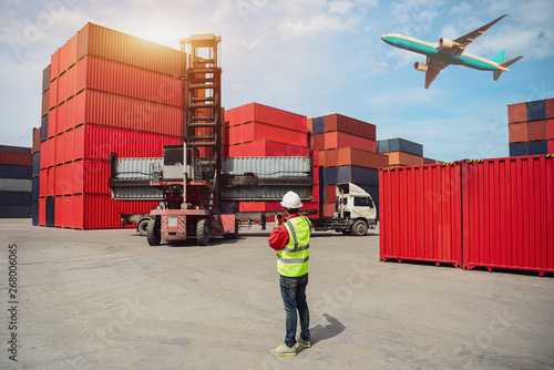 Fotografie, Obraz  Foreman control loading containers box from cargo freight ship for import export