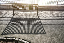Morning Sun Cast Lines Of Shadows On Asphalt Pavement Through Fence And Empty Bench By The River