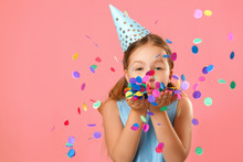 Cheerful Little Girl Celebrates Birthday. The Child Blows Confetti From The Hands. Closeup Portrait On Pink Coral Background.