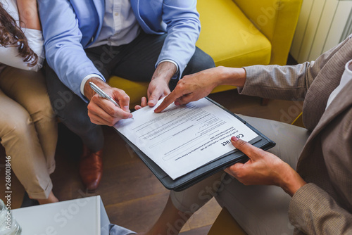 Fotografiet Young married couple signing real estate purchase contract  after consulting wit
