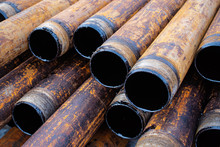 Salvaged Pipes And Casings Are Lined Up On Racks In Storage On A California Oil Lease. Drill Pipes With Oil Drops.
