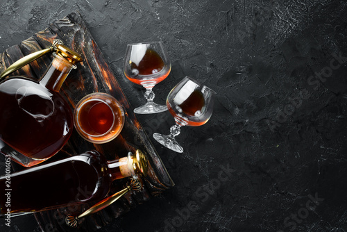 Foto auf Leinwand Alkohol A bottle of cognac and glasses on a black background. Brandy. Top view. Free space for your text.