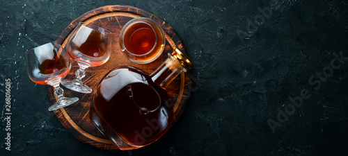 Cuadros en Lienzo A bottle of cognac and glasses on a black background