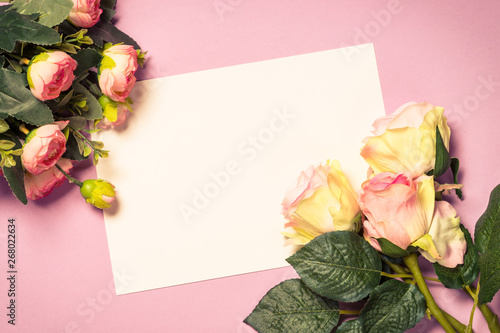 Tuinposter Europa Empty paper sheet and flowers on pink background.