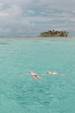 Two Person Swimming At The Beach During Daytime
