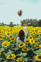 Woman Standing In The Middle On Sunflower Field While Throwing Her Hat On The Air
