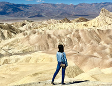 Woman Standing On Brown Stand Near Mountains During Daytime