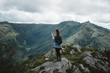 woman standing on the cliff of mountain
