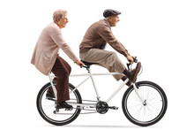 Senior Man And Woman Riding A Tandem Bicycle With Legs Up