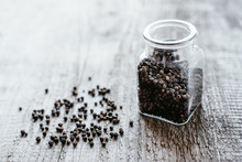Black Pepper Is Poured From A Glass Jar On A Wooden Surface