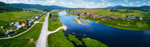 Aerial Panorama Of The River Of Belaya With The Villages On Its Green Coasts And Asphalt Road Along The River